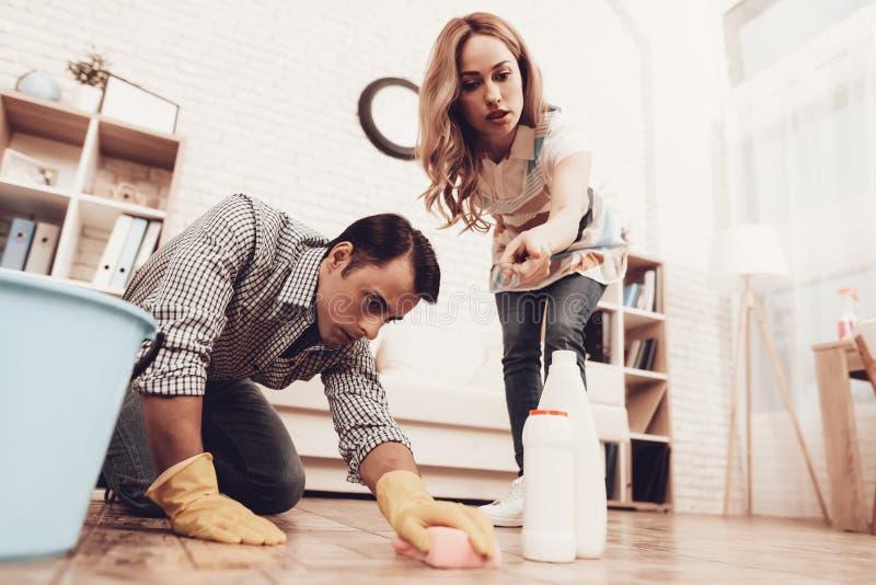 Rengörande golv för kvinnakontrollman i lägenhet royaltyfria bilder