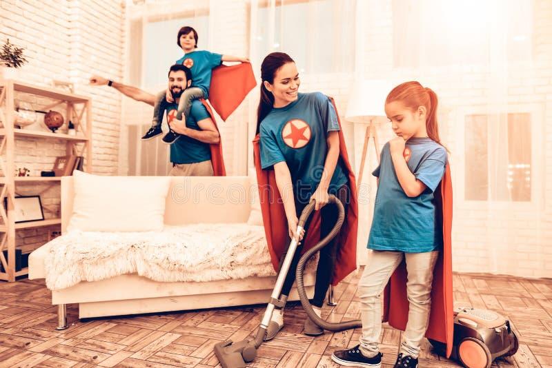 Rengörande hus för gullig Superherofamilj med ungar royaltyfria bilder
