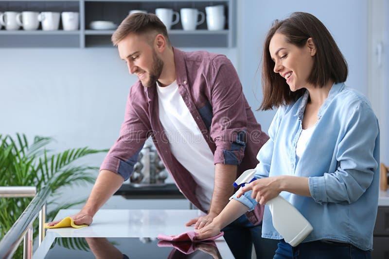 Rengörande kök för unga par tillsammans arkivbilder