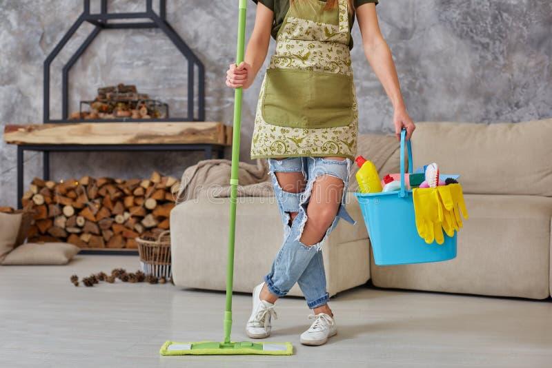rengörande service Hink med svampar, kemikalieflaskor och moppapinne Kantjusterad bild av en kvinna med en golvmopp på arkivfoton
