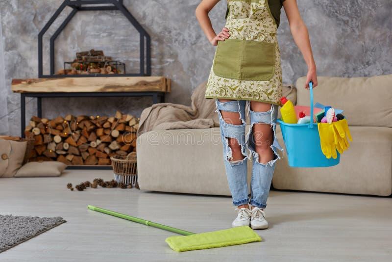 rengörande service Hink med svampar, kemikalieflaskor och moppapinne Kantjusterad bild av en kvinna med en golvmopp på arkivfoto