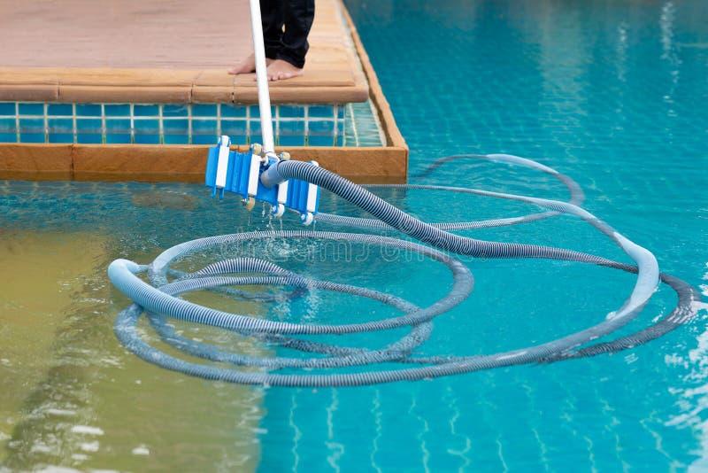 Rengörande simbassäng för arbetare med vakuumröret i morgonen fotografering för bildbyråer