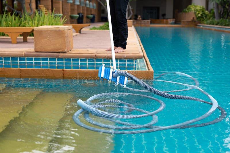 Rengörande simbassäng för arbetare med vakuumröret i morgonen arkivbild