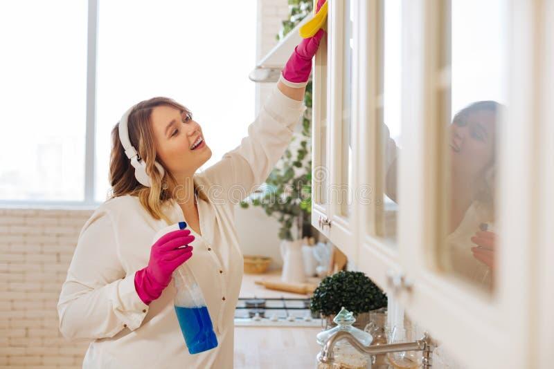 Rengörande skåp för positiv trevlig kvinna i köket arkivbilder