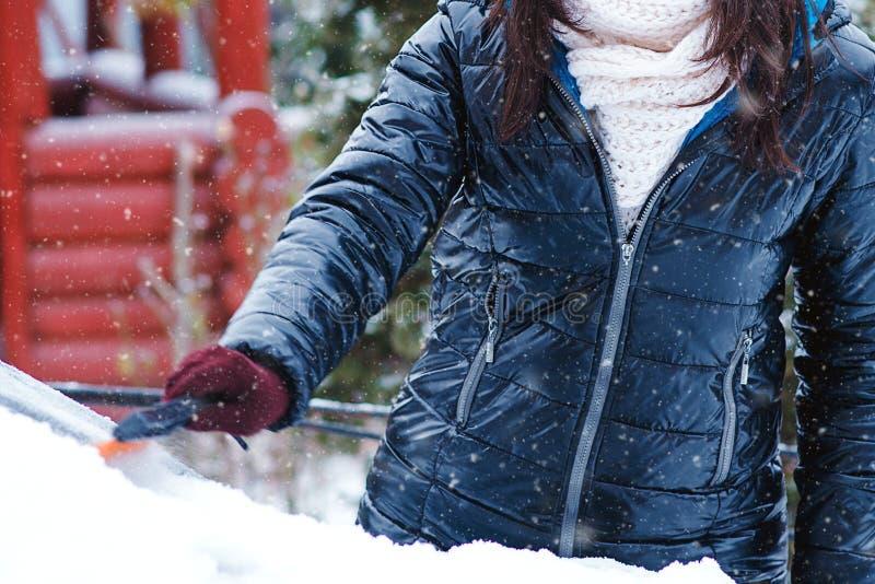 Rengörande snö för man från bilvindrutan med borsten, slut upp bil som tar bort snowkvinnan Snöig vinterväder Bil i snö efter royaltyfri bild