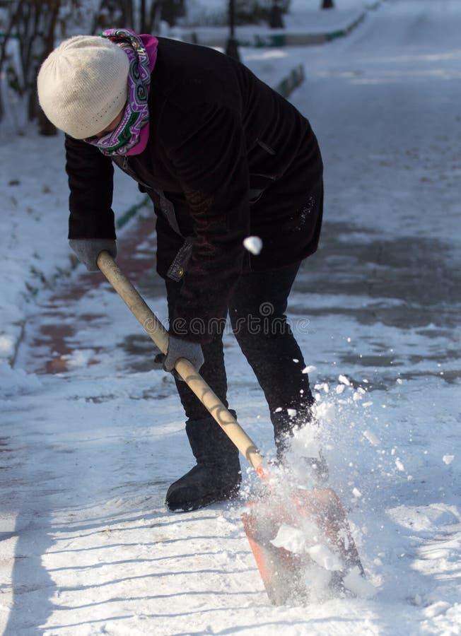 Rengöringar för funktionsduglig kvinna snöar skyffeln i naturen fotografering för bildbyråer
