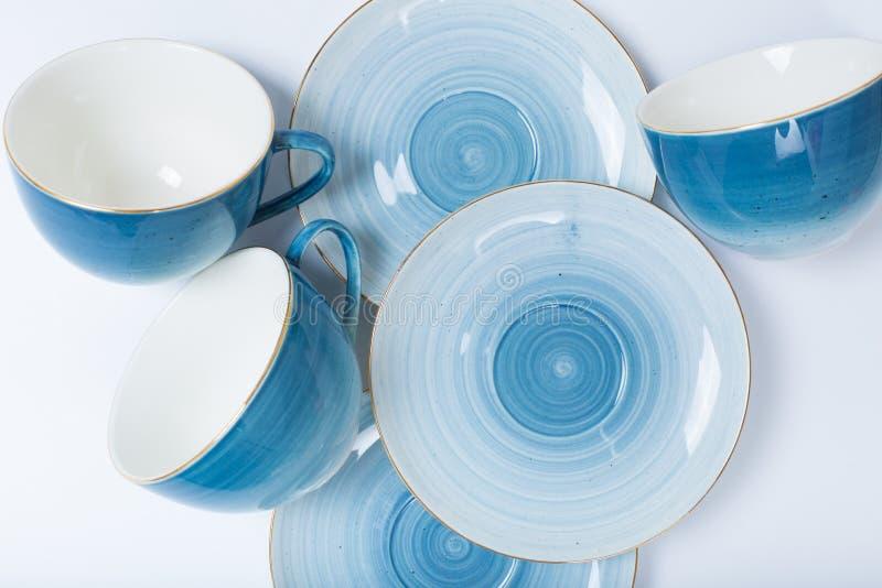 Rengöringdisk, kaffe eller teservis Överflöd av eleganta porslinkoppar och tefat på vit bakgrund royaltyfri bild