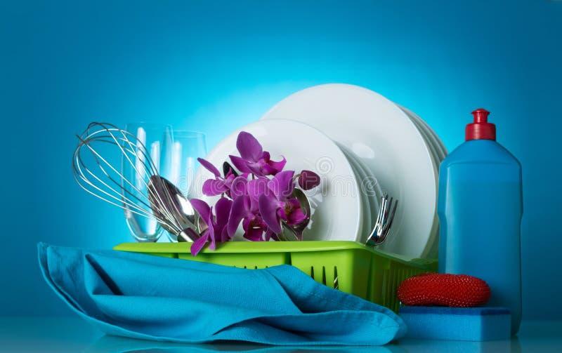 Rengöringdisk på torken, tvättmedel, svampar och servett, på blått arkivbild