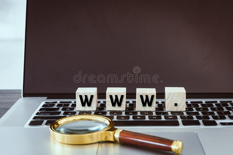 Rengöringsdukwebbläsare WWW med det träkuben och förstoringsglaset på bärbar datortangentbordet, teknologikommunikation och webbp royaltyfri bild