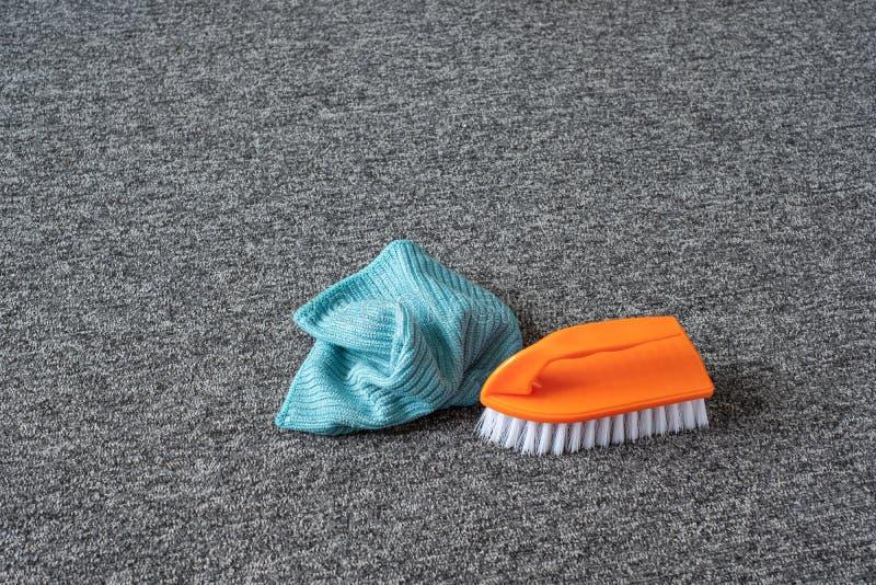Rengöringspensel och mikrofiberduk på den grå mattan fotografering för bildbyråer
