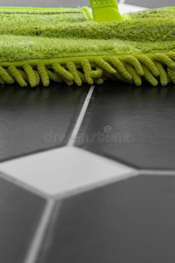 Reng?rande belagt med tegel golv med ett gr?nt huvud f?r torr golvmopp arkivbilder