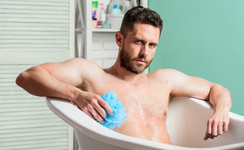 Reng?rande delar f?rkroppsligar egg toilet Sitter den muskul?sa torson f?r mannen i badkar applicera genomskinlig fernissa f?r om arkivfoto