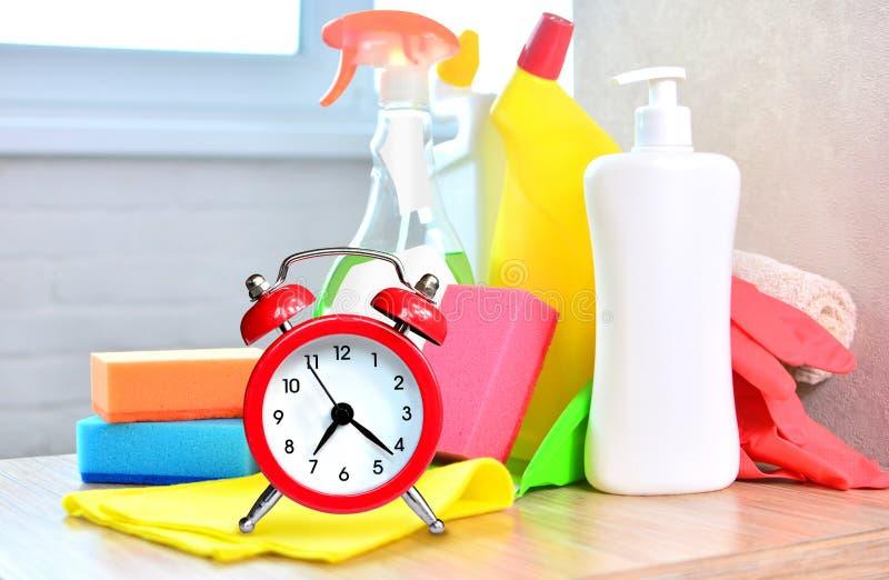 reng?rande service Hushållkemikalieer och stor röd klocka arkivbild