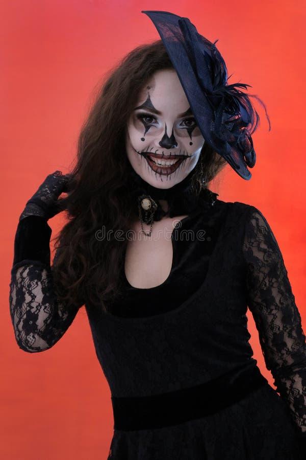 Renivellement de Veille de la toussaint La belle fille sexy dans la robe noire et le chapeau mignon sourit Fond rouge Vêtements d photographie stock