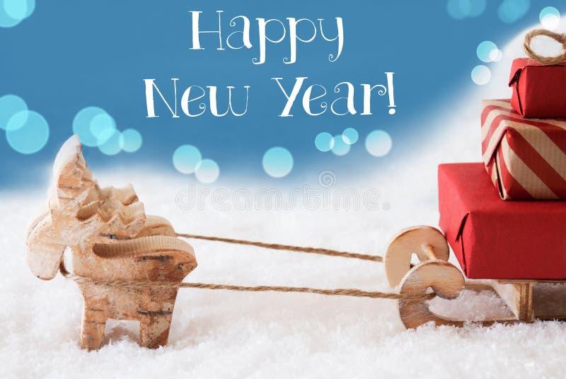 Renna, slitta, fondo blu-chiaro, buon anno del testo immagine stock