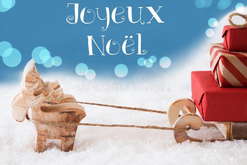 Renna, slitta, fondo blu-chiaro, Joyeux Noel Means Merry Christmas fotografie stock