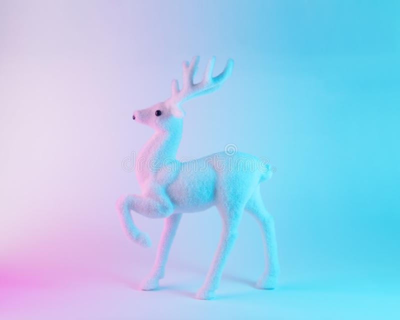 Renne blanc dans des couleurs olographes de gradient audacieux vibrant Concept minimal d'art de Noël et de nouvelle année image stock