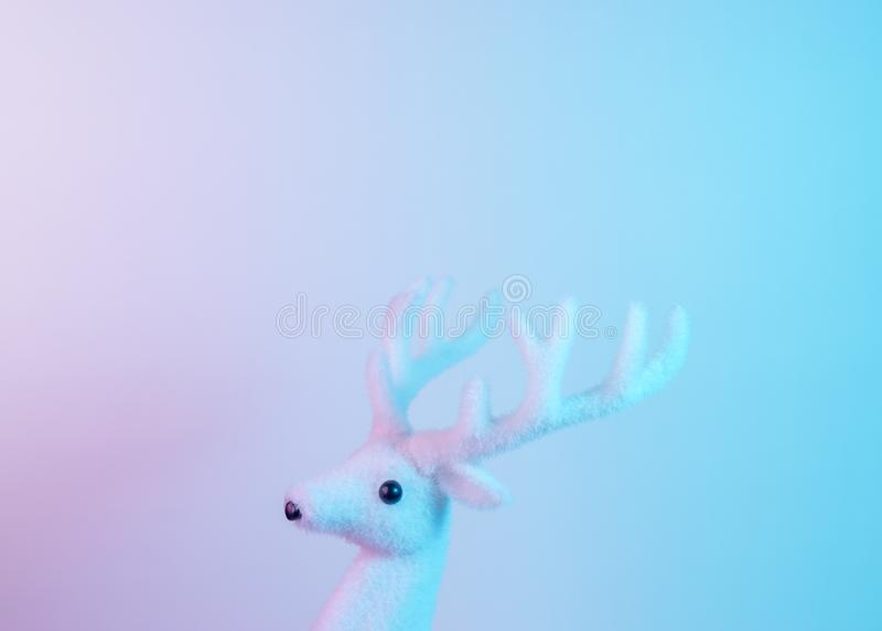 Renne blanc dans des couleurs olographes de gradient audacieux vibrant Concept minimal d'art de Noël et de nouvelle année photos stock
