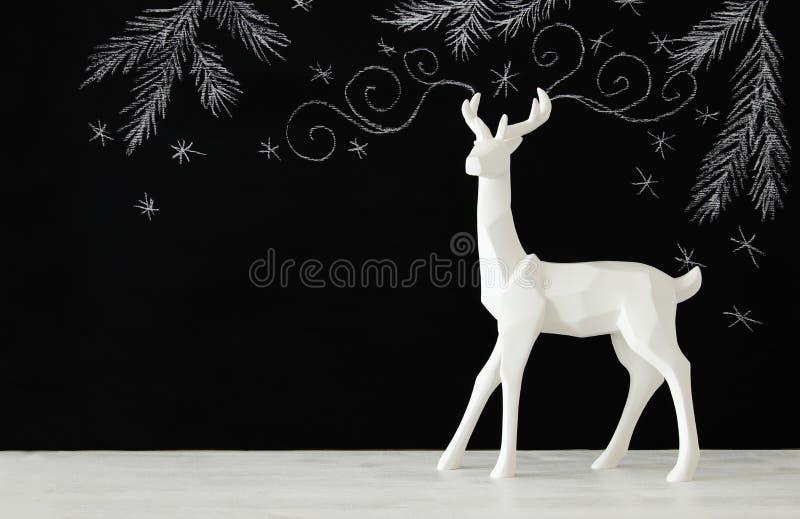 Renne blanc sur la table en bois au-dessus des illustrations tirées par la main de craie de whith de fond de tableau image libre de droits