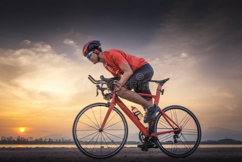 Rennradradfahrer-Mannradfahren Das Radfahren trägt Eignungsathleten-Reitfahrrad auf einer offenen Straße zum Sonnenuntergang zur  lizenzfreies stockfoto