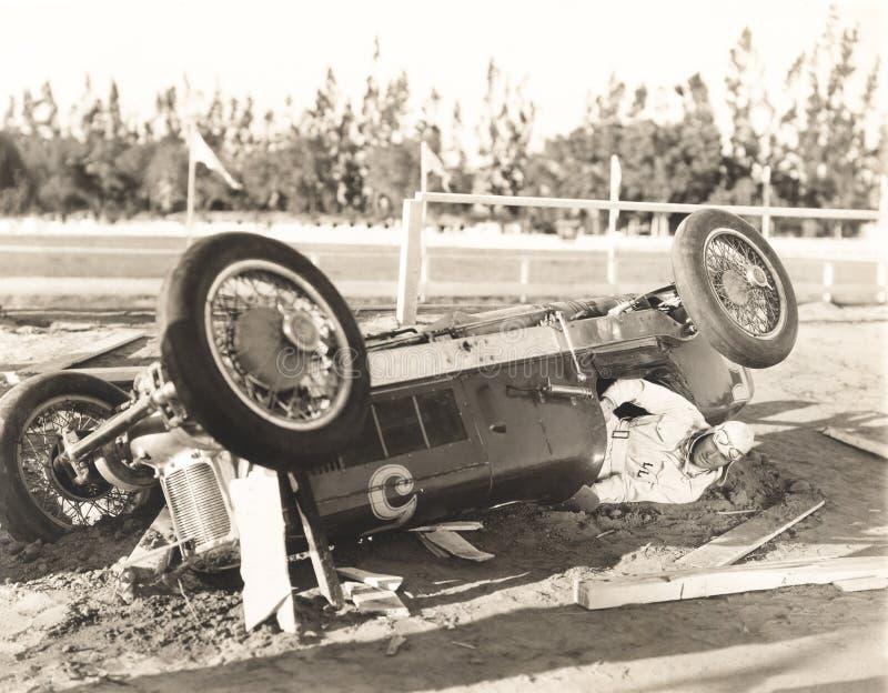 Rennwagenfahrer fest in umgeworfenem Auto lizenzfreies stockfoto