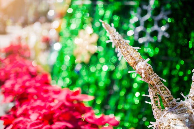 Reno adornado con el árbol rojo borroso del poinesettia para el fondo del día de fiesta de la Navidad imágenes de archivo libres de regalías
