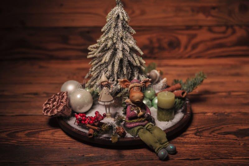 Reno y pequeña muchacha del duende en un arreglo de la Navidad foto de archivo libre de regalías