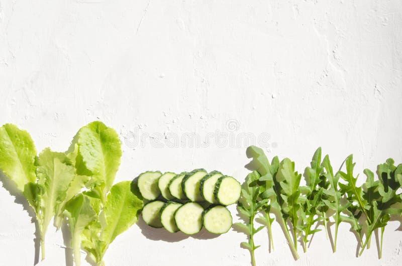 Renommée faite de tranches vertes de laitue, d'arugula et de frsh de cucumnber sur la surface blanche L'espace vide pour la conce photographie stock