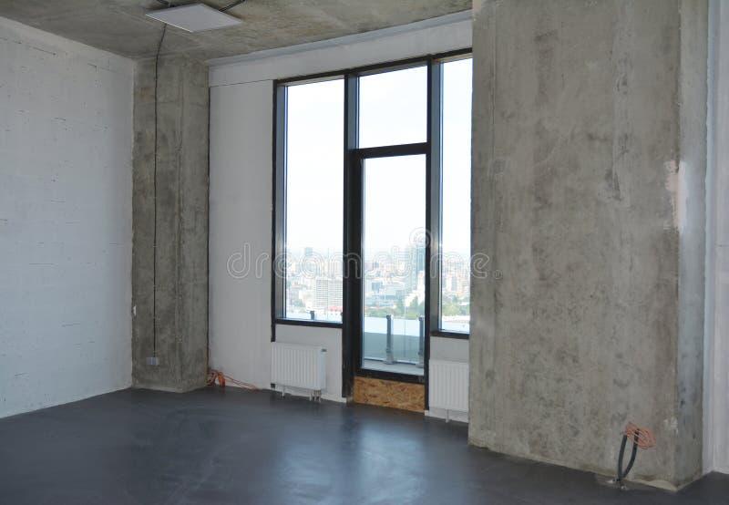 Renovação de salas no edifício do apartamento com uma janela e uma sacada em construção, chão de betão, pilar no canto e foto de stock royalty free