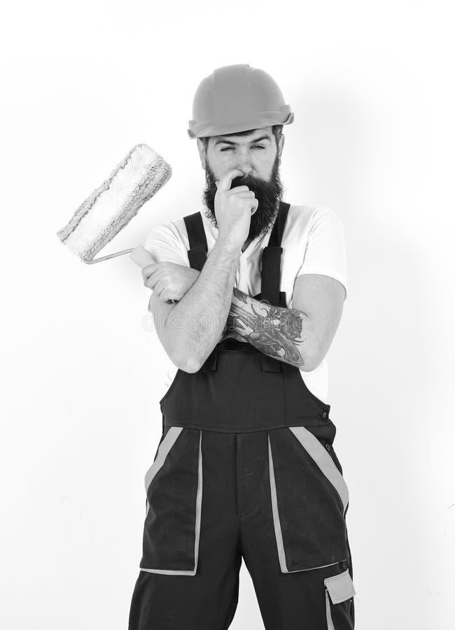 Renovação e conceito da decoração Homem com barba e bigode no capacete e macacões com rolo de pintura Decorador sobre fotos de stock royalty free