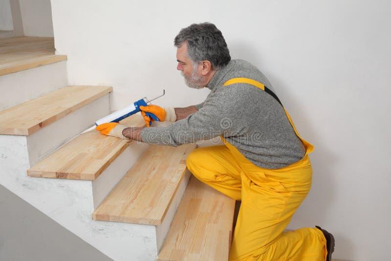 Renovação home, calafetando escadas de madeira com silicone fotos de stock