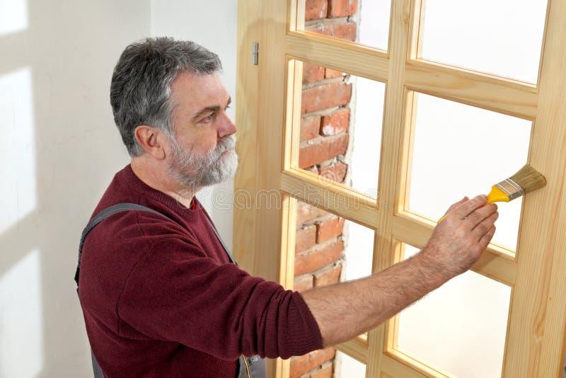 Renovación casera, trabajador que pinta la puerta de madera, barnizando imagenes de archivo