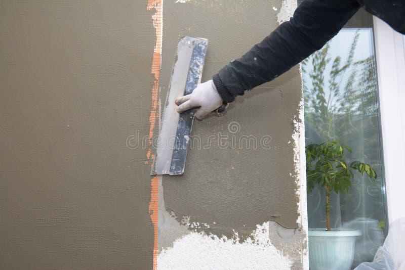 Renovación de la pared de la casa, aseguramiento con capas de recubrimiento, malla de refuerzo, aislamiento de espuma de poliesti fotos de archivo libres de regalías