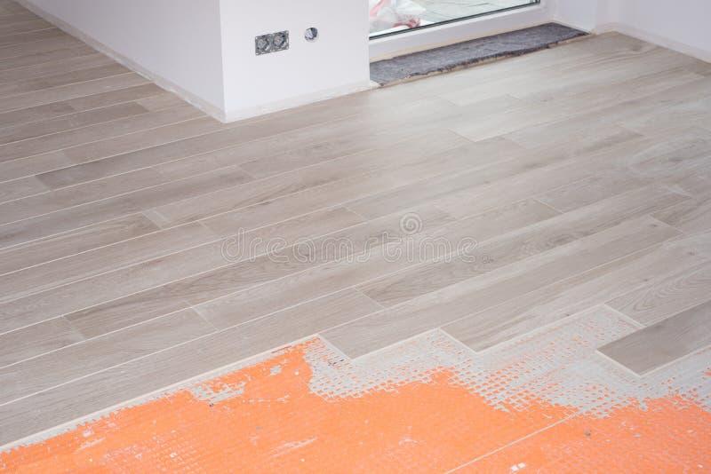 Renovación del piso con las baldosas cerámicas en el diseño de madera imagen de archivo