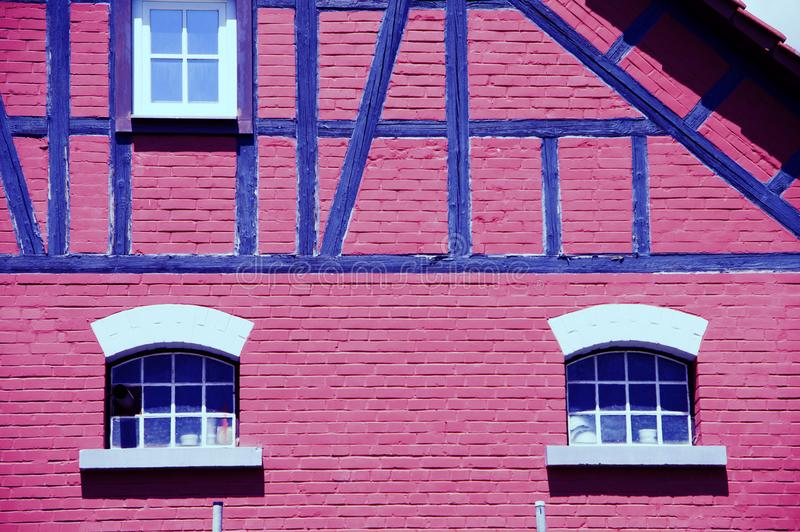 Old manicured barn with red wall and blue truss. Renovated agricultural building with half-timbered facade, Cowshed with masonry half-round window topple, big royalty free stock photography