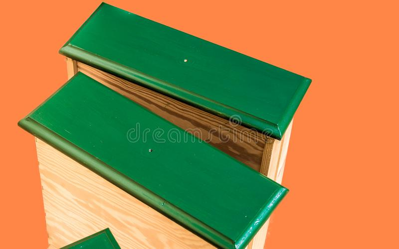 Renovated, green painted and repaired drawers of an old ugly used cupboard, ready for recycling, released in front of an orange ba stock images
