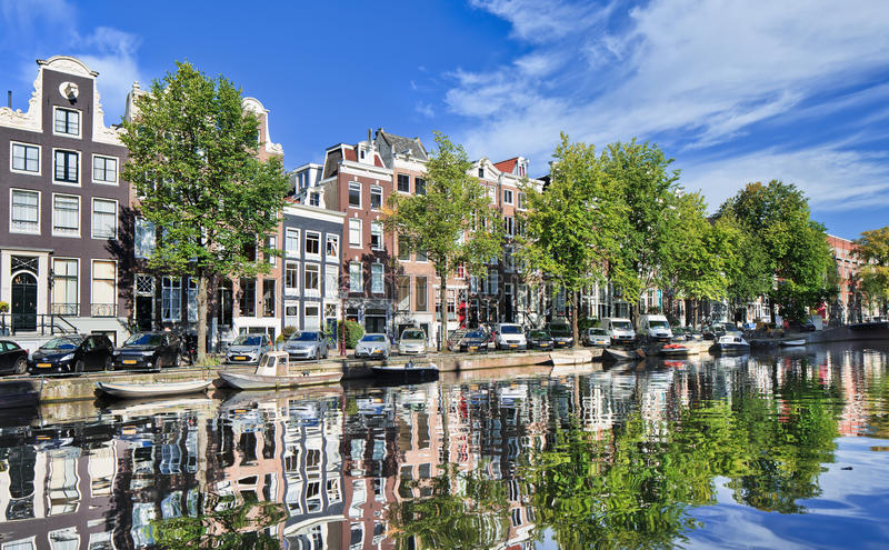 Renovated mansions reflected in a canal, Amsterdam, Netherlands stock photos