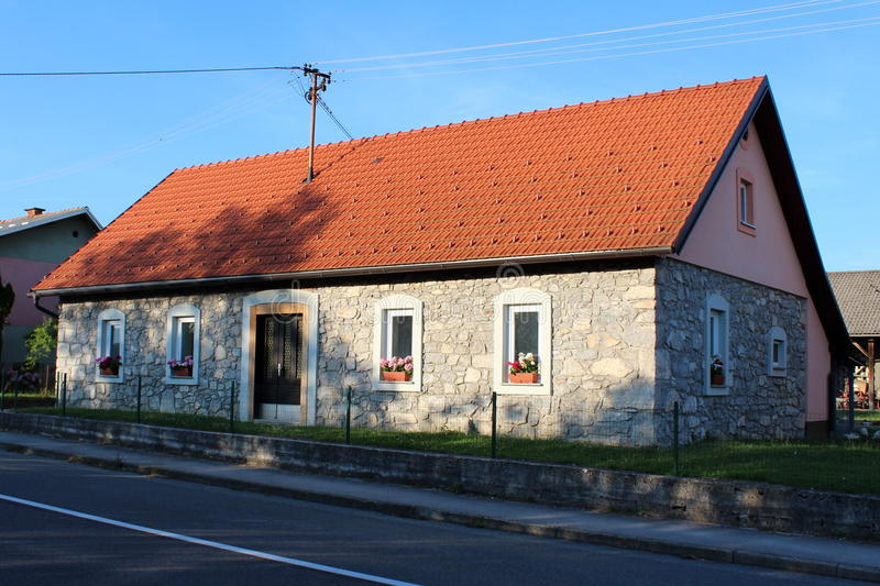 Renovated stone house. Renovated small stone house with new red roof at sunset with tree shadows and grass in front next to local road stock image