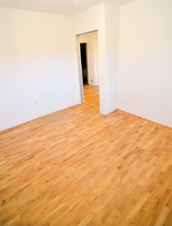Renovating old apartment and parquet wooden hard floor. Empty room with white walls. Shiny new floor royalty free stock photography