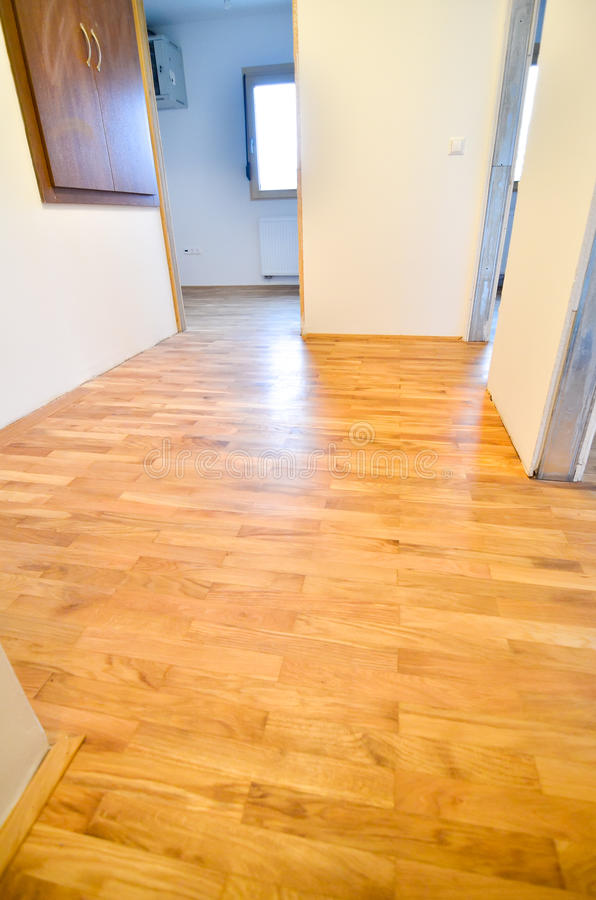 Renovating old apartment and parquet wooden hard floor. Empty room with white walls. Shiny new floor royalty free stock photos