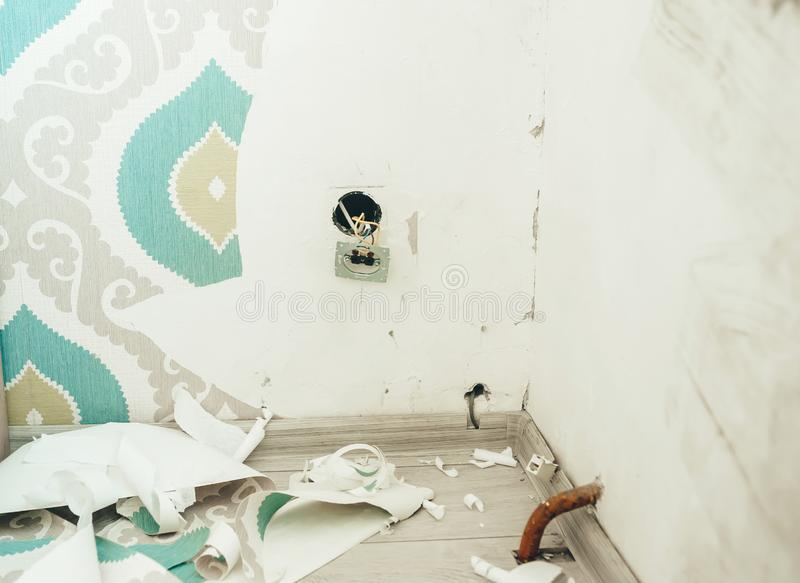 Removing of old wallpaper from wall in home room stock image