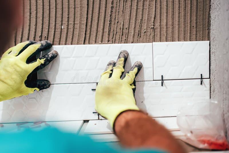 Renovation close-up details - hands of worker installing ceramic tiles on bathroom walls. Construction, renovation close-up details - hands of worker installing royalty free stock images