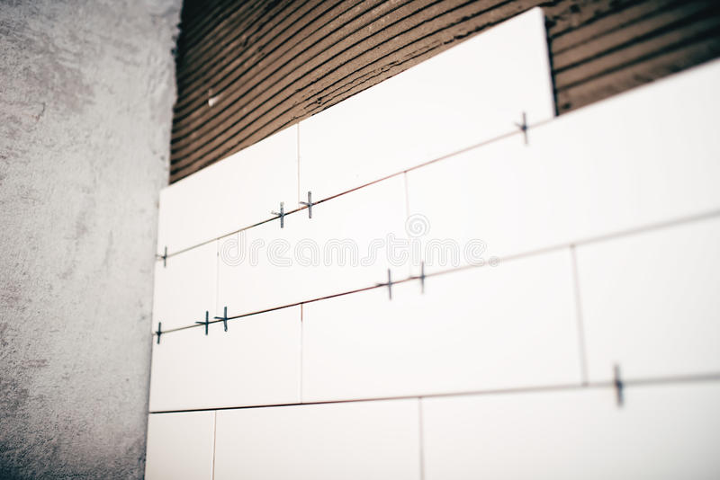 Renovation, close up details of plastic distancer on ceramic tiles and adhesive on walls stock image