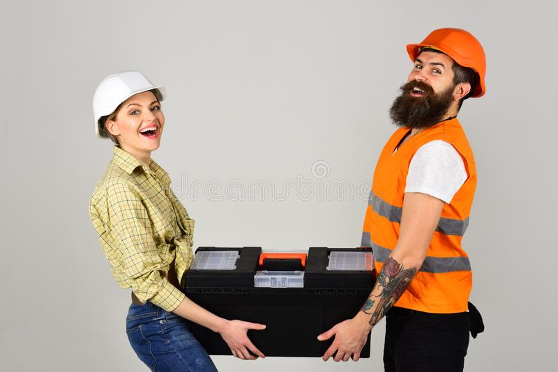 Renovation and construction. Couple of construction workers. Couple of hard workers. Pretty woman and bearded man in royalty free stock image