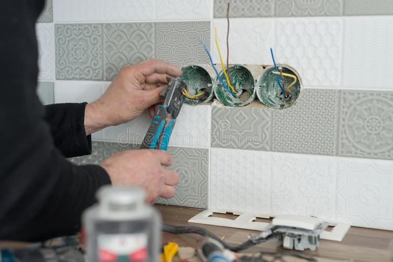 Renovation and construction in kitchen, close-up of electricians hand installing outlet on wall with ceramic tiles using royalty free stock photos