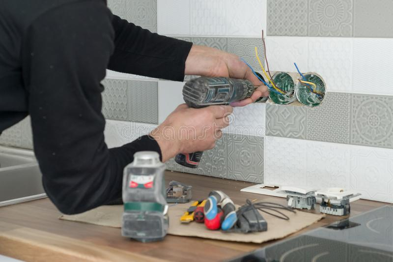 Renovation and construction in kitchen, close-up of electricians hand installing outlet on wall with ceramic tiles using royalty free stock images