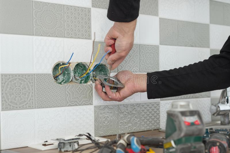 Renovation and construction in kitchen, close-up of electricians hand installing outlet on wall with ceramic tiles using royalty free stock photography