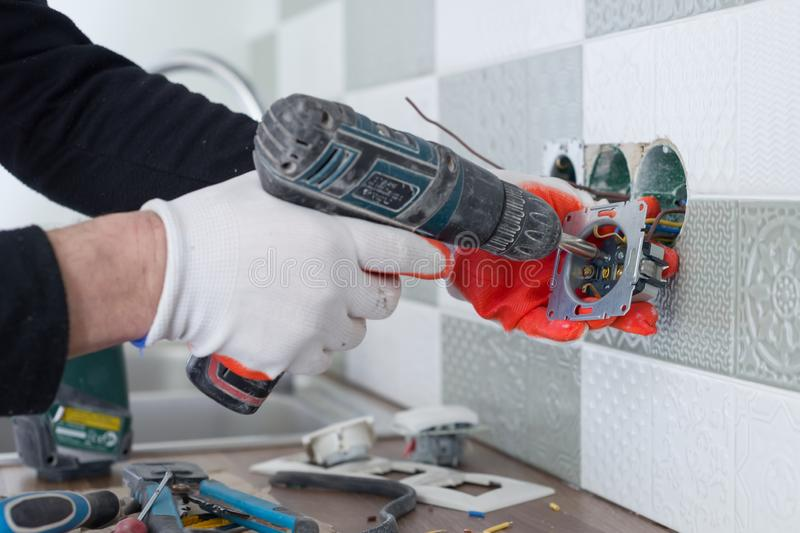 Renovation and construction in kitchen, close-up of electricians hand installing outlet on wall with ceramic tiles using royalty free stock image