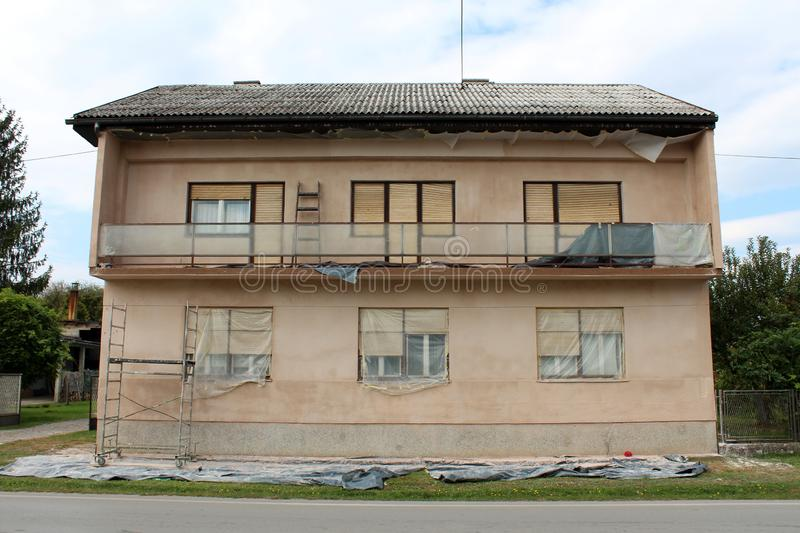 Renovation of facade on family house with long front balcony partially covered with protective nylon next to paved road. On warm cloudy day royalty free stock image