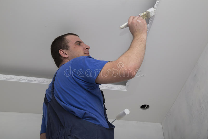 Renovation of house interior. Man worker painting. Renovation of house interior. Man worker painting the ceiling holding roller and brush with paint royalty free stock photos